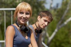 Adolescentes positivos jovenes con los auriculares Foto de archivo libre de regalías