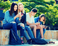 Adolescentes positivos que juegan con los teléfonos móviles Imagen de archivo