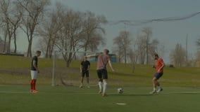 Adolescentes positivos que juegan a fútbol en campo de deportes metrajes