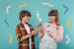 Adolescentes positivos que sonríen y que comen las melcochas Fotografía de archivo