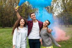Adolescentes preciosos que presentan con humo coloreado Foto de archivo libre de regalías