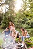Adolescentes que acampan, cocinando la carne en hoguera Fotografía de archivo