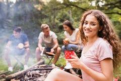 Adolescentes que acampan, cocinando la carne en hoguera Fotografía de archivo libre de regalías