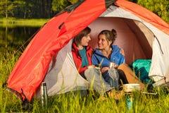 Adolescentes que acampan que se sientan y que abrazan en tienda Fotografía de archivo libre de regalías