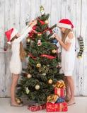 Adolescentes que adornan el árbol del Año Nuevo en casa Fotos de archivo