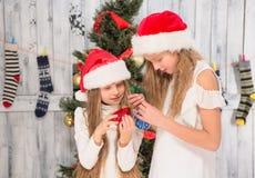 Adolescentes que adornan el árbol del Año Nuevo en casa Fotos de archivo libres de regalías