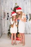 Adolescentes que adornan el árbol del Año Nuevo en casa Foto de archivo libre de regalías