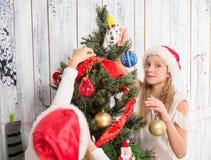 Adolescentes que adornan el árbol del Año Nuevo en casa Imagenes de archivo