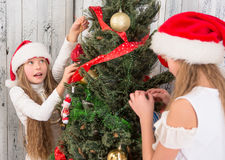 Adolescentes que adornan el árbol del Año Nuevo en casa Imágenes de archivo libres de regalías