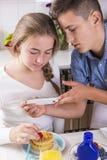 Adolescentes que adornan las crepes con la baya Fotos de archivo libres de regalías