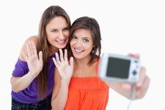Adolescentes que agitan para una cámara digital Fotos de archivo libres de regalías