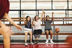 Adolescentes que animan a los muchachos que juegan a baloncesto Foto de archivo libre de regalías