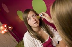 Adolescentes que aplican maquillaje Foto de archivo libre de regalías