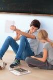 Adolescentes que aprenden por una pizarra en sala de clase Imágenes de archivo libres de regalías