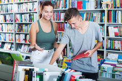 Adolescentes que buscan los nuevos libros Foto de archivo libre de regalías