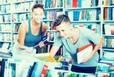 Adolescentes que buscan los nuevos libros Imagen de archivo libre de regalías