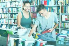 Adolescentes que buscan los nuevos libros Imágenes de archivo libres de regalías