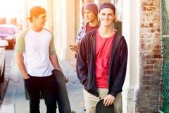 Adolescentes que caminan abajo de la calle en día de verano Foto de archivo