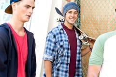 Adolescentes que caminan abajo de la calle en día de verano Fotografía de archivo