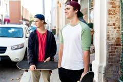 Adolescentes que caminan abajo de la calle en día de verano Imagenes de archivo