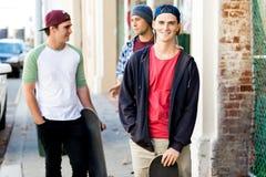 Adolescentes que caminan abajo de la calle en día de verano Fotos de archivo