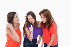 Adolescentes que cantan en un micrófono Fotografía de archivo libre de regalías
