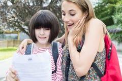 Adolescentes que celebran buen resultado del examen Imagen de archivo libre de regalías