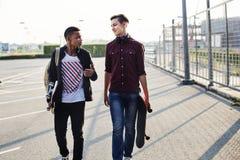Adolescentes que celebran caminar del monopatín Imagen de archivo libre de regalías