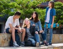 Adolescentes que charlan al aire libre en ciudad Fotos de archivo