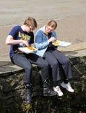Adolescentes que comem o peixe com batatas fritas, Bakewell Fotos de Stock Royalty Free