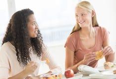 Adolescentes que comen bocados en cantina de universidad Foto de archivo
