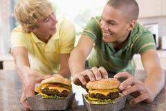 Adolescentes que comen las hamburguesas Imagen de archivo libre de regalías