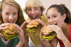 Adolescentes que comen las hamburguesas Imágenes de archivo libres de regalías