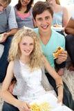 Adolescentes que comen las hamburguesas y las fritadas Fotografía de archivo