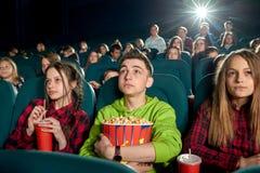 Adolescentes que comen las palomitas y que miran la película en cine imagenes de archivo