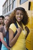 Adolescentes que consiguen en el autobús escolar Imágenes de archivo libres de regalías