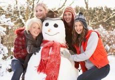 Adolescentes que construyen el muñeco de nieve Foto de archivo libre de regalías