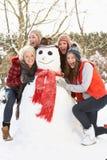 Adolescentes que construyen el muñeco de nieve Imagen de archivo libre de regalías