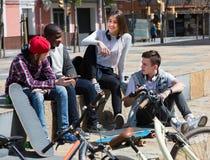 Adolescentes que conversam perto das bicicletas Imagem de Stock