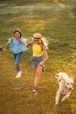 Adolescentes que corren con el perro Fotografía de archivo libre de regalías