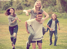 Adolescentes que corren en césped verde en parque Foto de archivo libre de regalías