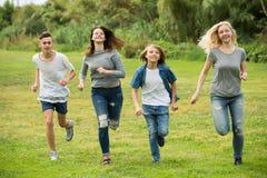 Adolescentes que corren en césped verde en parque Fotografía de archivo libre de regalías