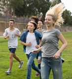 Adolescentes que corren a través de césped verde en verano en parque Imagen de archivo libre de regalías