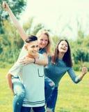Adolescentes que corren a través de césped verde en verano en parque Fotos de archivo libres de regalías