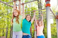 Adolescentes que cuelgan en la barra brachiating junto Fotos de archivo