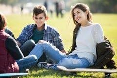 Adolescentes que cuelgan hacia fuera al aire libre y que discuten algo Imágenes de archivo libres de regalías