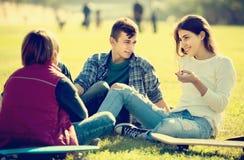 Adolescentes que cuelgan hacia fuera al aire libre y que discuten algo Foto de archivo