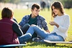 Adolescentes que cuelgan hacia fuera al aire libre y que discuten algo Foto de archivo libre de regalías