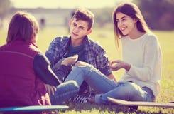 Adolescentes que cuelgan hacia fuera al aire libre y que discuten algo Fotos de archivo libres de regalías