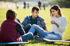 Adolescentes que cuelgan hacia fuera al aire libre y que discuten algo Imagen de archivo libre de regalías